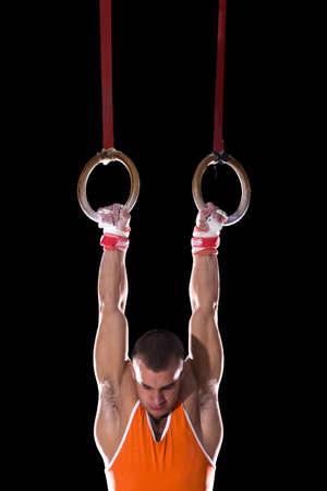 gymnastique: Homme gymnaste effectuer sur les anneaux de gymnastique