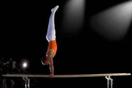 gimnasia: Gimnasta masculino realizar parada de manos en las barras paralelas, vista lateral LANG_EVOIMAGES