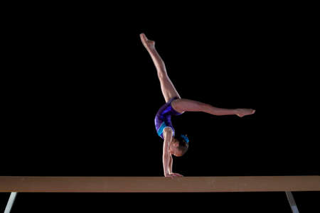 female gymnast: Young female gymnast (9-11) performing handstand on balance beam, side view LANG_EVOIMAGES