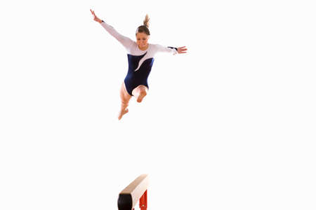 balance beam: Female gymnast performing jump on balance beam, low angle view LANG_EVOIMAGES