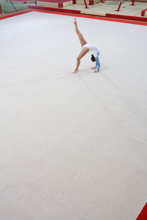 elevated view: Female gymnast performing backbend, elevated view