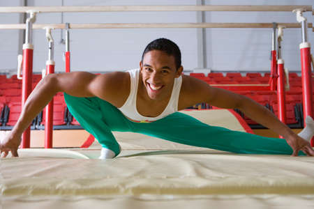 agility people: Male gymnast stretching in gymnasium, smiling, portrait