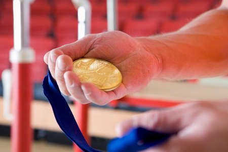 blue and gold: Male gymnast holding gold medal, close-up of hands