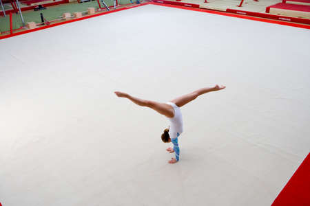 performing: Female gymnast performing handstand, elevated view LANG_EVOIMAGES