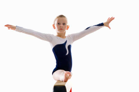 balance beam: Young female gymnast (9-11) performing on balance beam, portrait LANG_EVOIMAGES