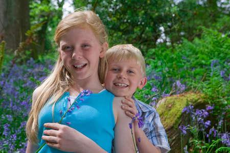 bluebell: Children sitting on log among bluebell flowers