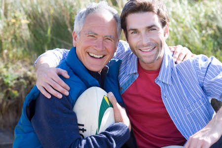 adult offspring: Portrait of two men holding rugby ball on beach