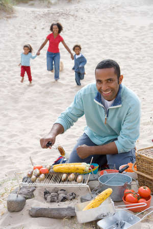 grill tongs sausage: Portrait of father preparing barbecue on beach, family running in background