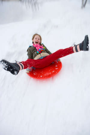 legs spread: Young girl sledding down snow slope
