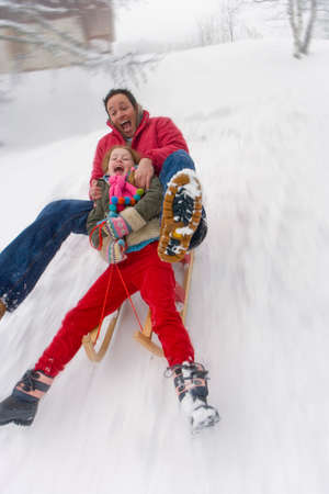 legs spread: Father and daughter sledding down snow slope LANG_EVOIMAGES