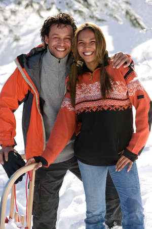mixed race couple: Portrait of mixed race couple with snow sled