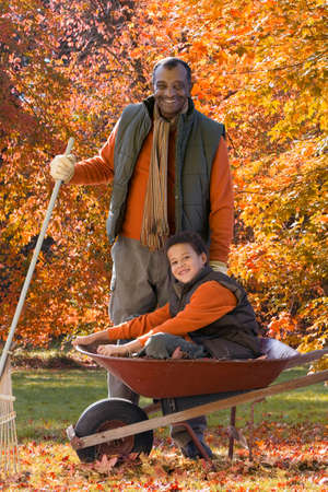 yard work: African man and grandson doing yard work in autumn