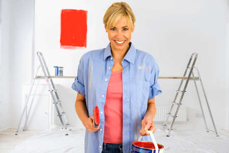 paint swatch: Smiling woman holding paint can with red paint swatch on wall in background LANG_EVOIMAGES