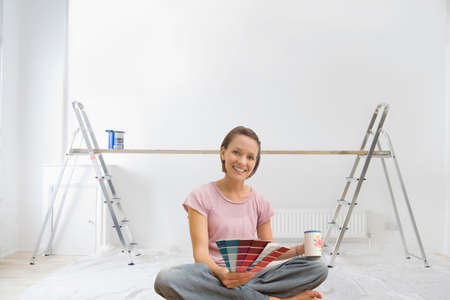paint swatch: Smiling woman holding paint swatches in living room with ladders and wood plank in background