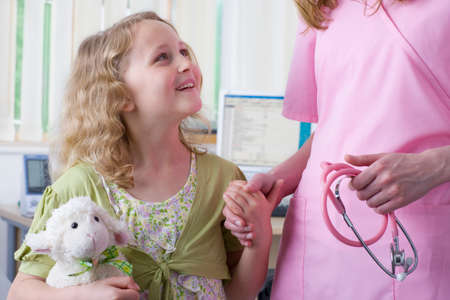 examination room: Smiling girl with stuffed animal holding nurseճ hand in examination room LANG_EVOIMAGES