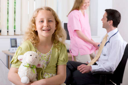 examination room: Girl smiling in examination room with doctor and nurse in background LANG_EVOIMAGES
