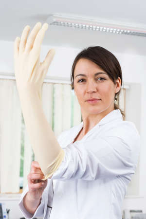 rubber glove: Doctor putting on rubber glove with attitude LANG_EVOIMAGES