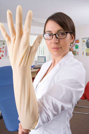 surgical coat: Doctor putting on surgical glove with attitude in examination room