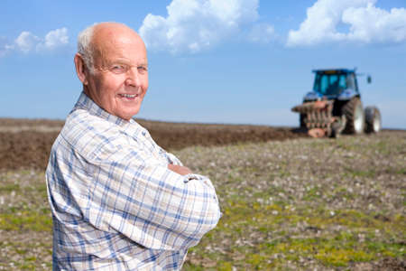 plough: Farmer standing in field with tractor and plough in background