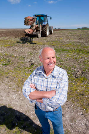 plough: Smiling farmer standing with arms crossed in field with tractor and plough in background LANG_EVOIMAGES