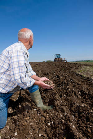 ploughing: Farmer cupping soil and watching tractor ploughing field