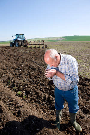 the ploughed field: Farmer smelling soil in ploughed field with tractor and plough in background