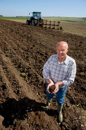 ploughed: Farmer cupping soil in ploughed field with tractor and plough in background
