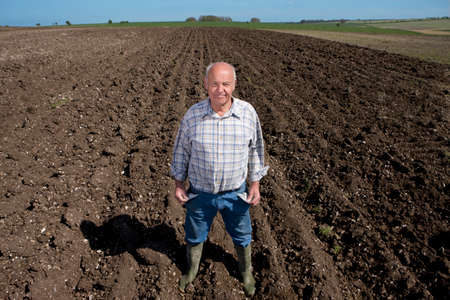the ploughed field: Farmer showing empty pockets in ploughed field LANG_EVOIMAGES