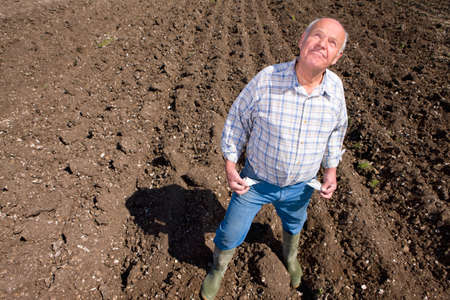 the ploughed field: Farmer showing empty pockets and looking up in ploughed field LANG_EVOIMAGES