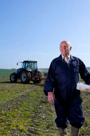 plough: Smiling farmer holding lunchbox in field with tractor and plough in background LANG_EVOIMAGES