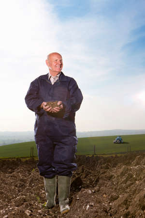 the ploughed field: Smiling farmer cupping soil in ploughed field LANG_EVOIMAGES