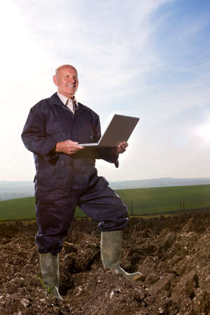 the ploughed field: Farmer using laptop in ploughed field