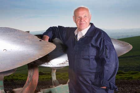 plough: Farmer leaning against plough in field LANG_EVOIMAGES