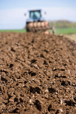 plough: Close up of ploughed field with tractor and plough in background LANG_EVOIMAGES