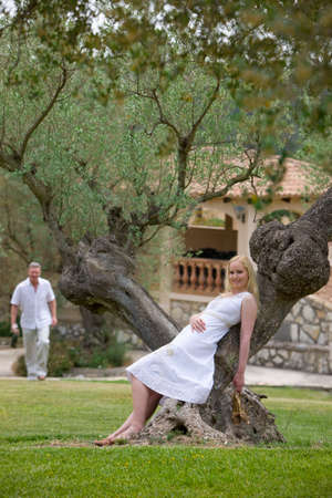 away from it all: Smiling woman leaning on olive tree trunk with man in background