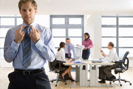 hope indoors luck: Businessman with fingers crossed and co-workers working in background