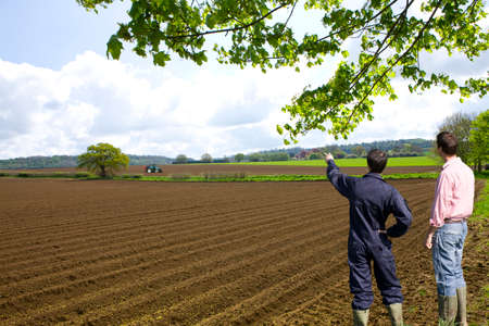 ploughed: Farmers viewing ploughed fields with tractor in distance
