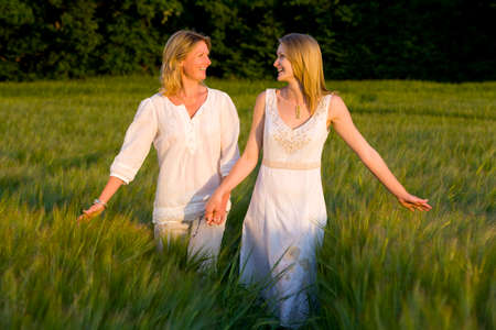 getting away from it all: Mother and teenage daughter walking through barley field