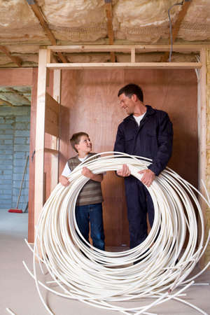 coveralls: Man in coveralls and young boy holding electrical cables