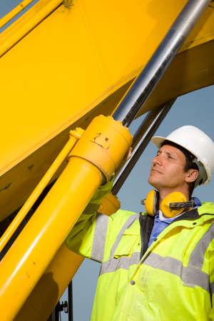 hydraulic: Construction worker examining hydraulic cylinders of bulldozer
