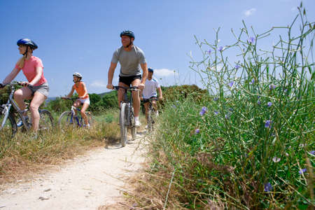 getting together: Couples riding bicycles on rural path