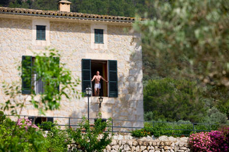 boxer shorts: Man in boxer shorts standing on sunny manor balcony