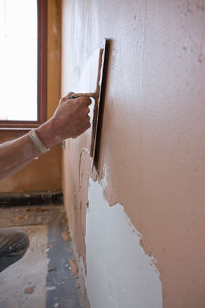 plastering: Man plastering wall with trowel LANG_EVOIMAGES