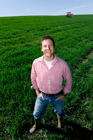 granjero: Sonreír agricultor de pie con las manos en los bolsillos en campo de trigo joven LANG_EVOIMAGES