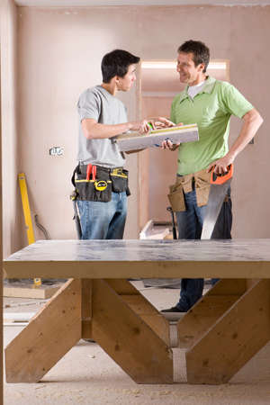 sawhorse: Men with tools talking next to sawhorse LANG_EVOIMAGES