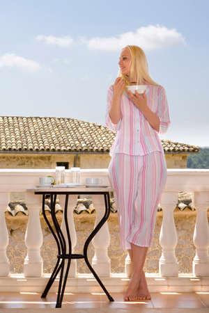 comiendo cereal: Mujer en los pijamas que come el cereal en el balc�n