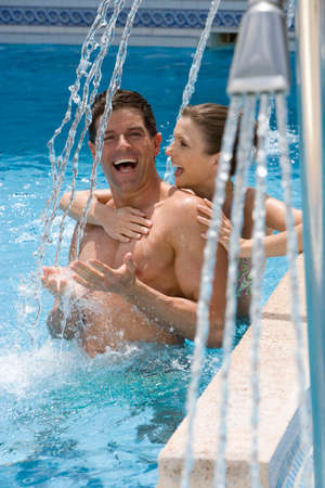 waist deep: Laughing couple standing under swimming pool shower LANG_EVOIMAGES