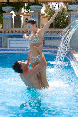 waist deep: Man lifting woman in swimming pool LANG_EVOIMAGES