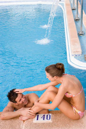 Woman ruffling manճ hair at edge of swimming pool