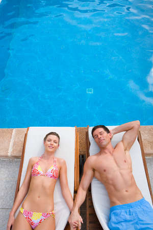 bare waist: Couple laying on lounge chairs and holding hands at poolside